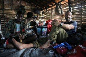 Ed Stafford and boatmen resting in Yeobi village hut.